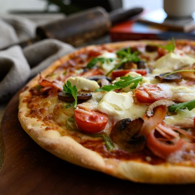 Pizza with fresh cream cheese, sautéed mushrooms, green peppers, cherry tomatoes and mozzarella cheese