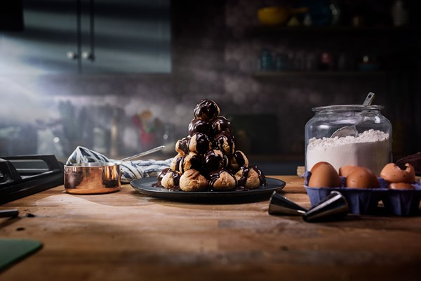 Profiterole tower with vanilla cream and chocolate sauce